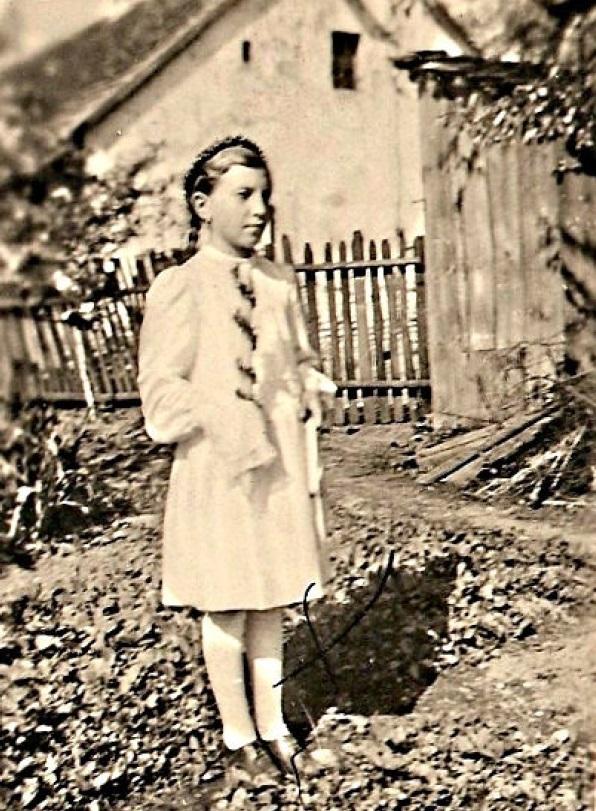 Na planie przednim Martusia Przeliorz w dniu przystąpienia do 1. Komunii. Z tyłu z prawej ustęp, w środku dom.